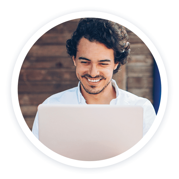 Man smiling and working on a laptop